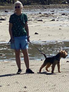 En bild på Gunbritt som står på en solig strand med en hund i koppel.