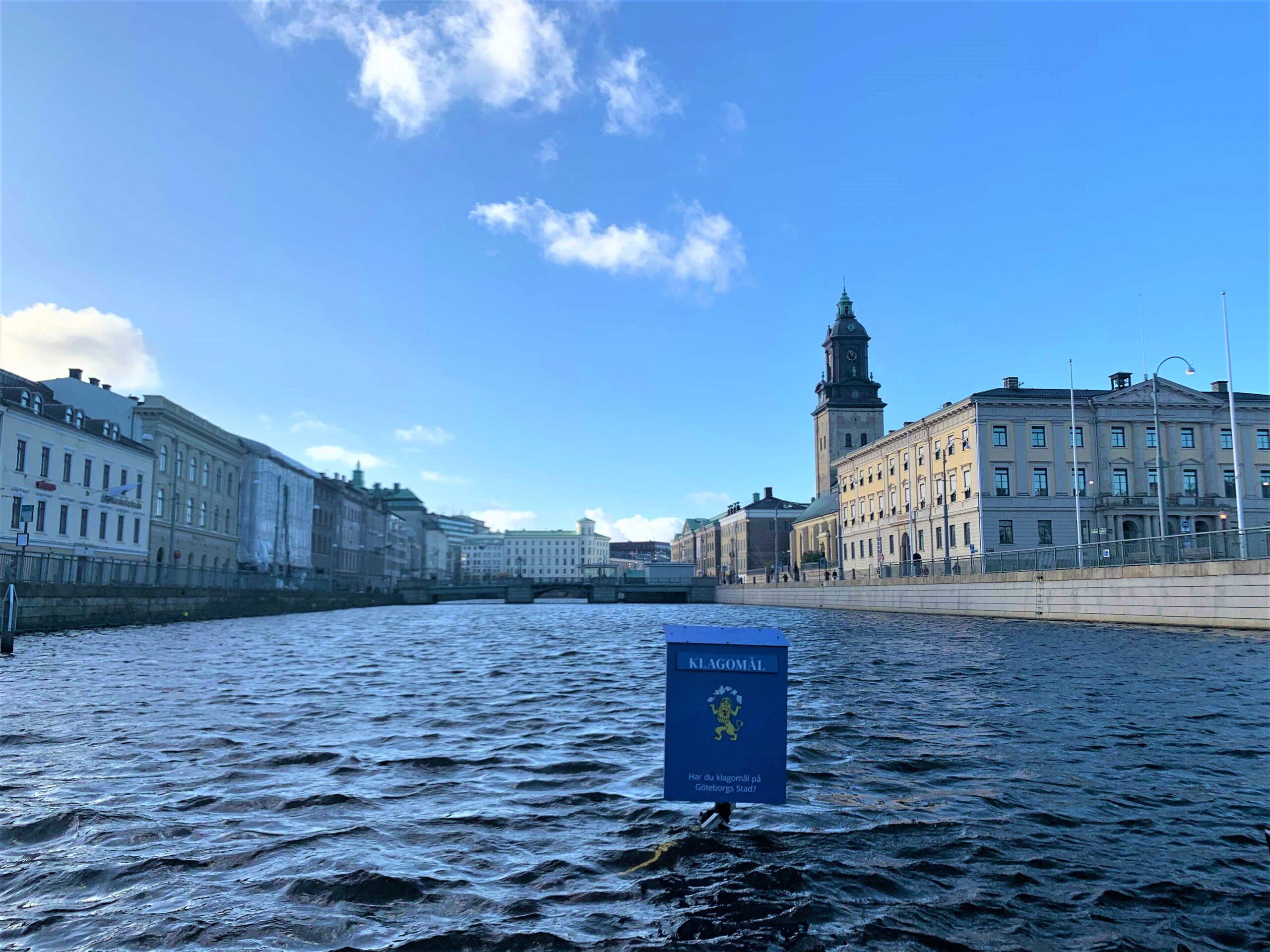 """En bild på kanalen vid Brunnsparken. Ute i vattnet sticker en blå brevlåda upp, med texten """"Har du klagomål till Göteborgs Stad?"""" på."""