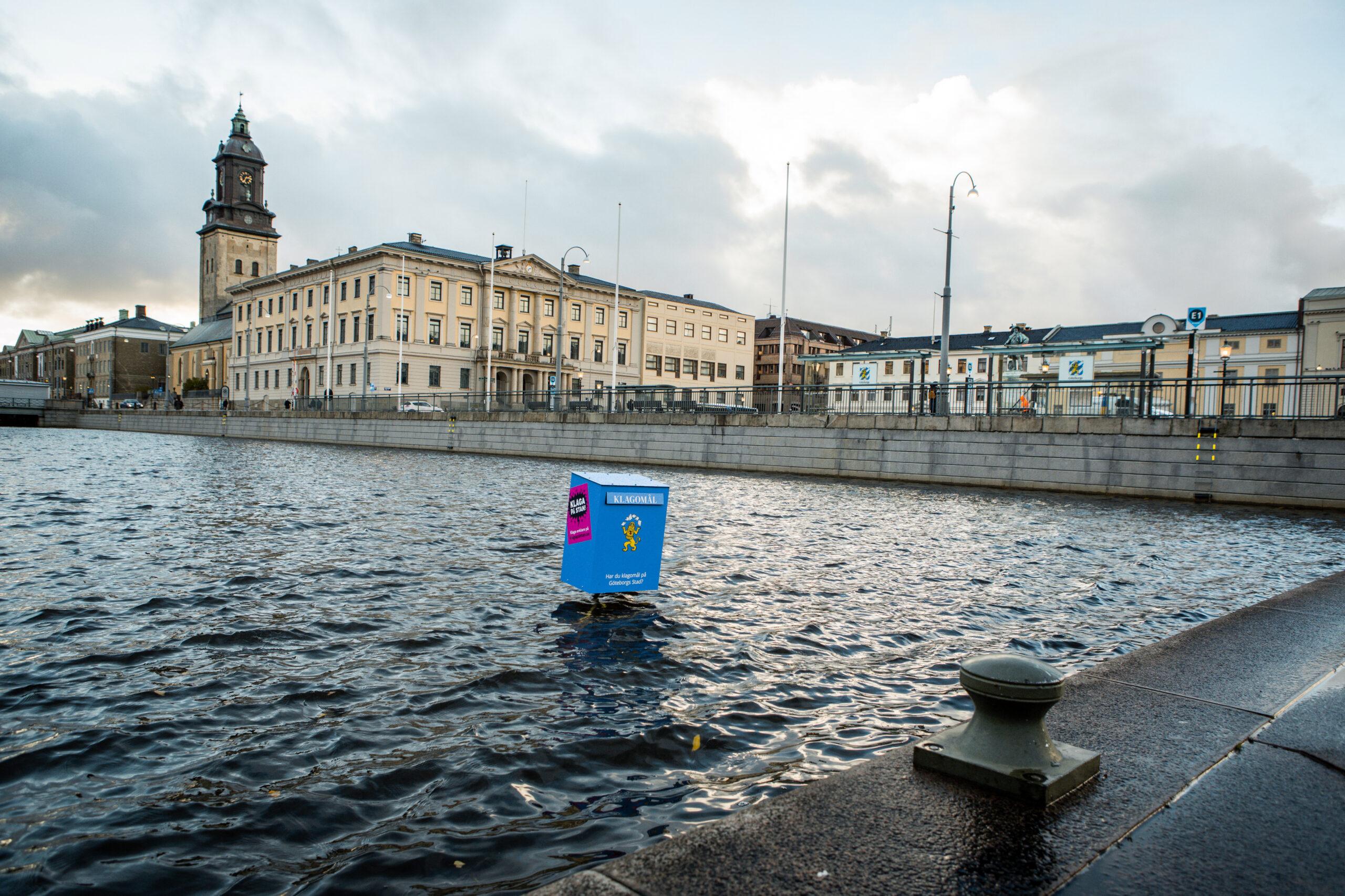 """Blå låda i kanalen vid rådhuset i Göteborg. På lådan syns texten """"Klagomål"""" och ett gult lejon som rycker på axlarna."""