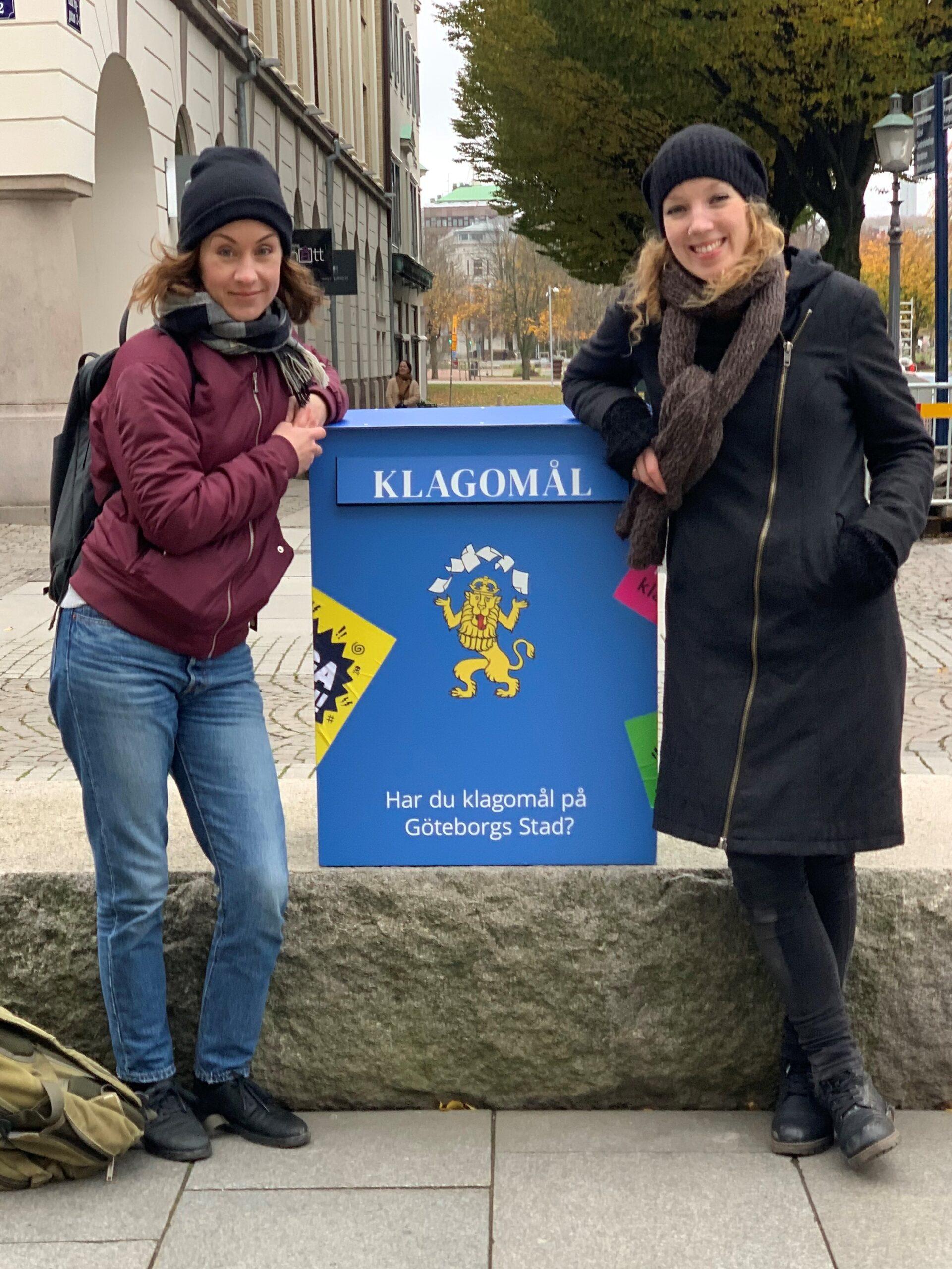 """Projektledarna Karin och My står på varsin sida om en blå låda med texten """"Klagomål"""" på. De lutar sig mot lådan och ler."""